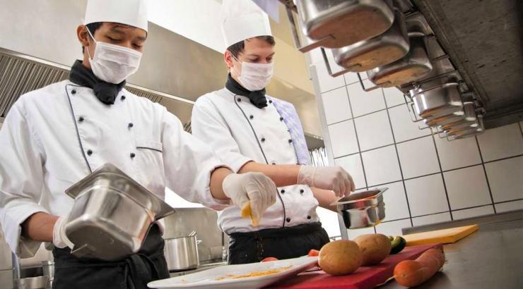 Restaurateurs portant des masques de protection contre le covid et préparant un plat.