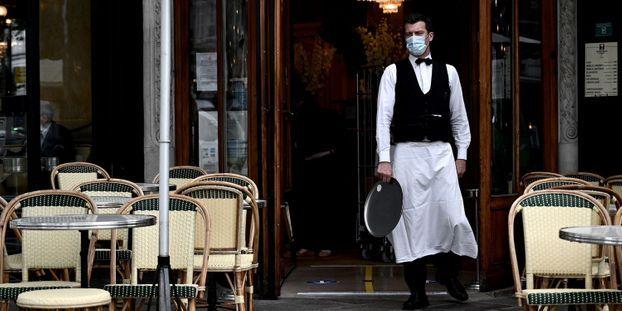 Un serveur portant un masque devant l'entrée d'un restaurant vide